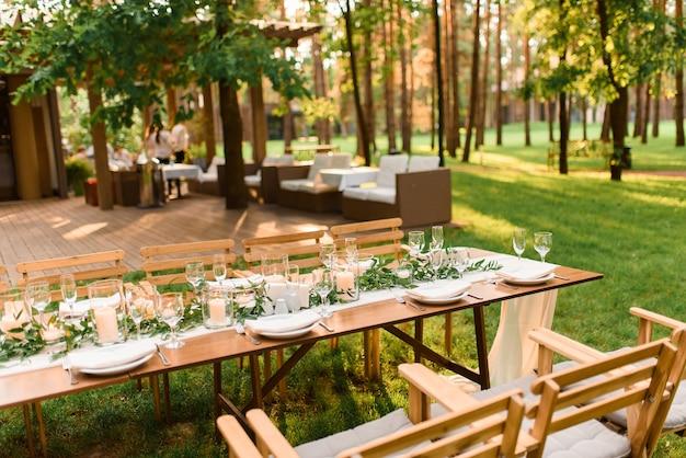 Организация свадебного банкета в лесу. деревенский стиль. зеленая ветка и свечи. празднование свадьбы.