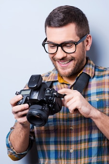 Setting the camera. portrait of confident young man in shirt holding camera while standing against grey background