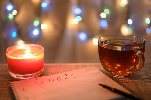 Постановка целей на следующий год с рождественским фоном и сверкающей гирляндой.