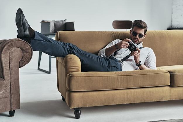 彼のカメラに設定します。ソファに横たわっている間彼の写真カメラを保持しているハンサムな若い男