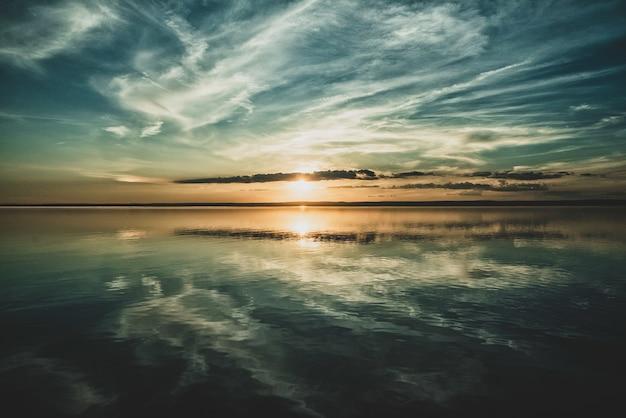 Заходящее солнце и облака неба отражаются в океане внизу
