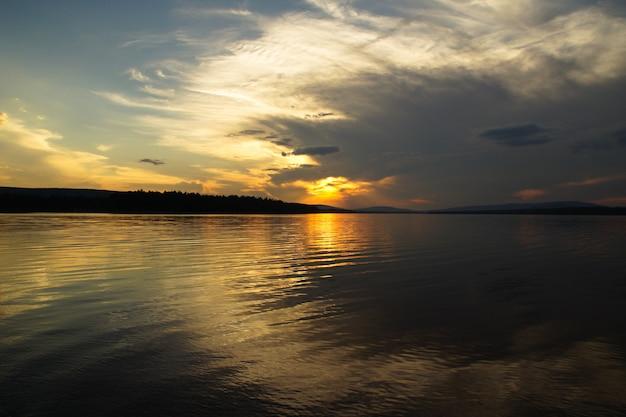 The setting sun shines through the passing thundercloud. sunset landscape reservoir