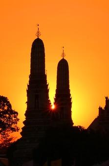 Setting sun shining through silhouette of wat arun temple spires in thailand