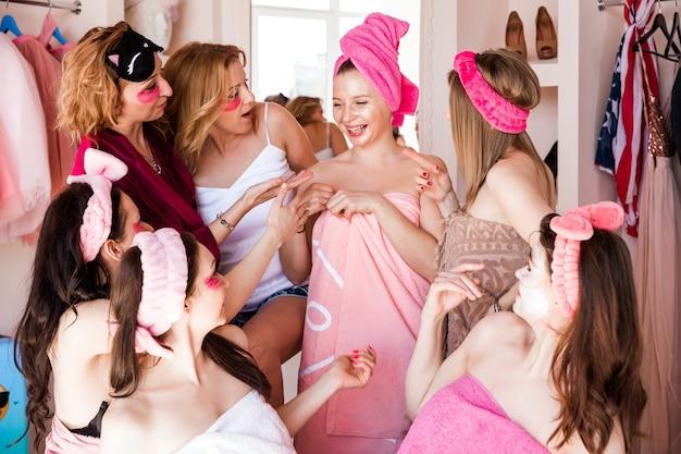 Семь красивых молодых женщин в розовых полотенцах, с косметическими повязками на голове