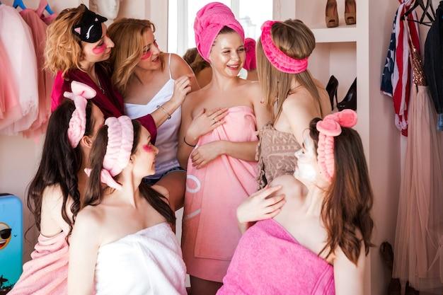 Семь красивых молодых женщин позируют на камеру с патчами под глазами и кремовой маской на лице. друзья собрались вокруг девушки и обсуждают ее маску для лица.