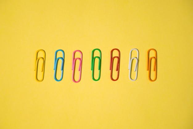 Семь различных цветных скрепок, изолированные на желтом фоне для использования элемента дизайна