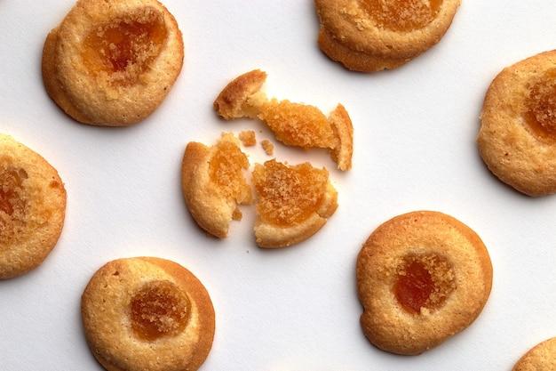 살구 잼이 들어간 7 개의 수제 쿠키가 비스듬히 균등하게 배열되어 있습니다. 흰색 배경에 고립