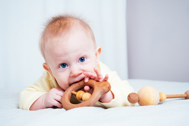 A seven-month-old girl with blue eyes lies on her stomach in a bright room and nibbles a wooden toy, the child's teeth are teething, gums are itching. concept of children's health.