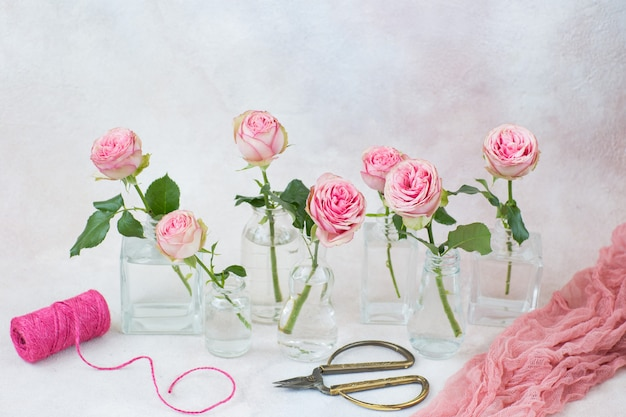 Seven roses in different types of vases, ribbon and scissors