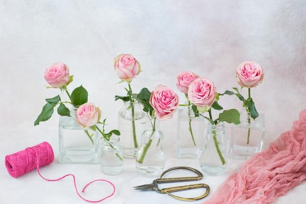 Семь роз в разных видах ваз, лента и ножницы
