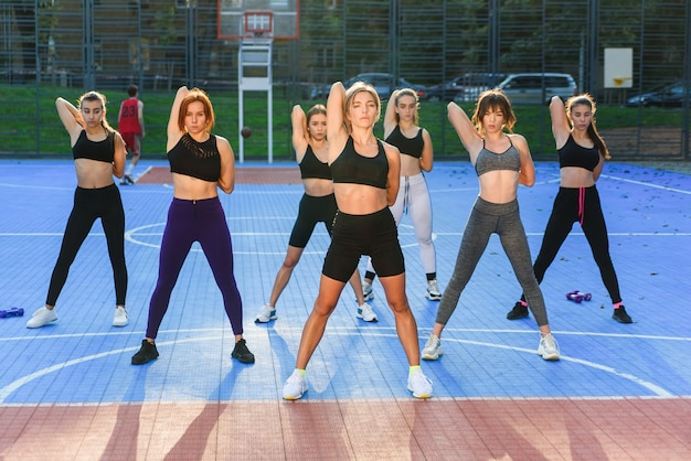 Seven slender sporty young women doing body tilts to left and right sides at the outdoors workout in urban park.