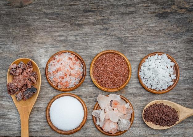 7種類の塩。木製の背景にボウルとスプーンで異なる塩