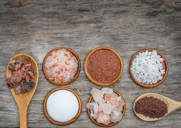 Seven types of salt. different salt in bowls and spoons on wooden background