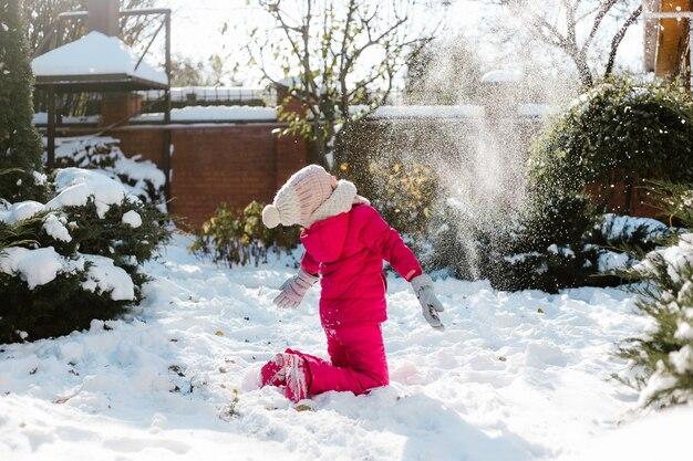冬の晴れた日に家の裏庭で雪遊びをしている冬服の7歳のかわいい女の子。