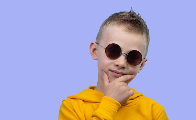 A seven-year-old boy in a yellow hoodie poses in front of a camera on a blue background