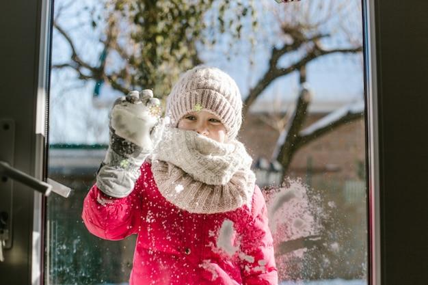 冬服を着た7歳のかわいい女の子が、ドアの外、雪を手にした通りに立って、笑顔で家の中を見ています。