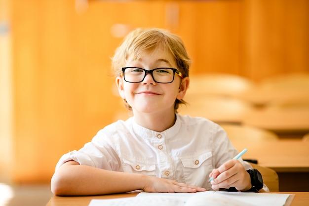학교에서 숙제를 쓰는 안경을 쓴 7 살짜리 아이