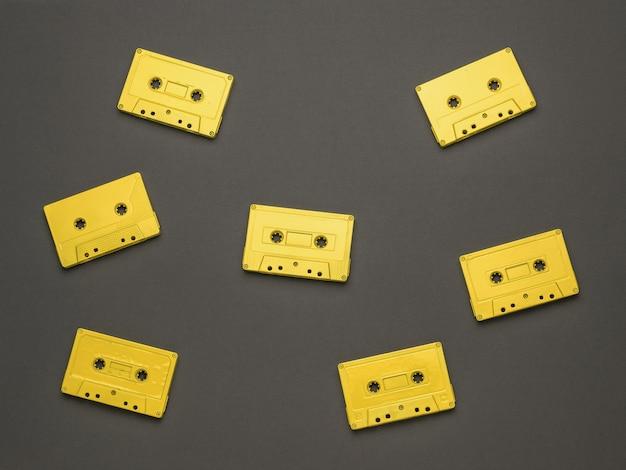 검정색 배경에 자기 테이프가 있는 7개의 노란색 카세트. 음악을 듣기 위한 세련된 복고풍 장비. 플랫 레이.