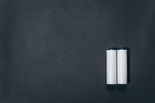 黒い紙のスペースにいくつかのaaブランクの白い電池