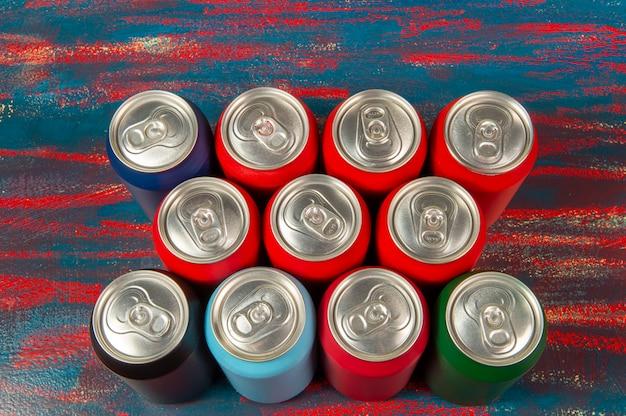 素朴なテーブルのさまざまな色のいくつかのアルミソーダ缶