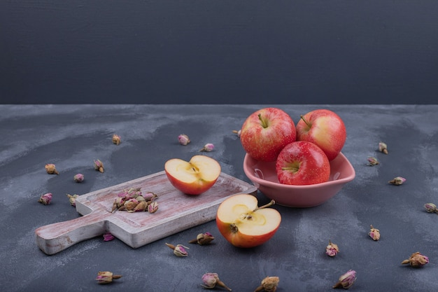 枯れたバラのプレート上のいくつかのリンゴは暗闇で上昇しました。