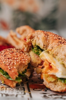 Several bagels cut in half with sesame and chia bread, inside it contains various ingredients such as tomato, ham, avocado, fresh cheese, chicken in strips.
