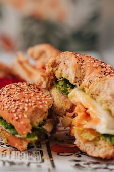 ゴマとチアパンで半分に切ったベーグルの中には、トマト、ハム、アボカド、フレッシュチーズ、チキンなどのさまざまな材料が入っています。