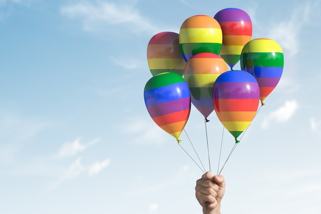 Several balloons with lgbt symbols. hand holds them. with copy space.