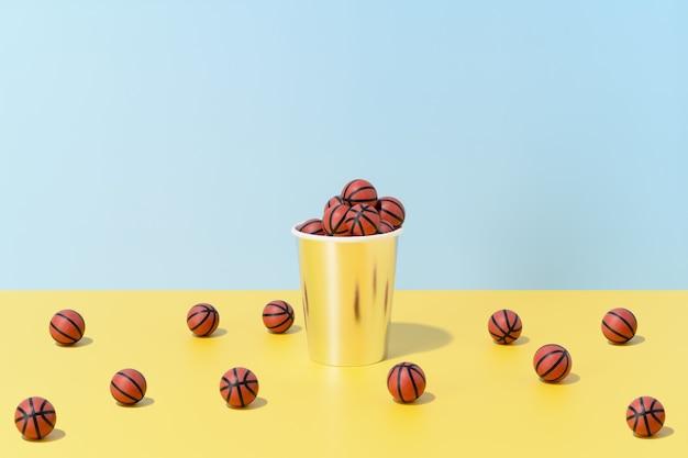 Несколько баскетбольных мячей в стакане и на полу на сине-желтом фоне. спорт и соревнования. 3d иллюстрации