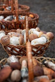 Несколько корзин с белыми грибами на земле