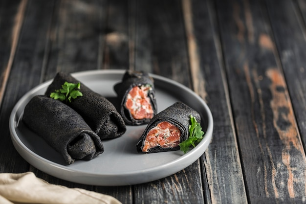 Several black cuttlefish ink pancakes with salmon and cheese filling on a gray plate