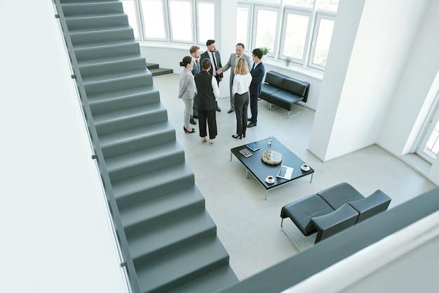 Несколько деловых партнеров стоят у лестницы в офисе и обсуждают стратегии своего нового проекта после подписания контракта.