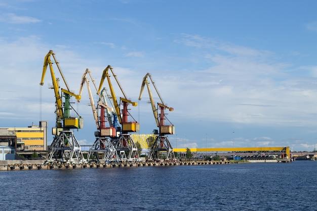 Несколько грузовых кранов стоят на берегу реки вента. вентспилс, латвия, балтийское море. копировать