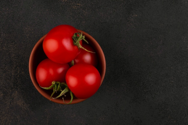 Several cherry tomatoes in a clay bowl on dark