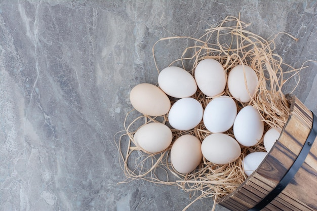 Several chicken fresh eggs on hay on marble background. high quality photo