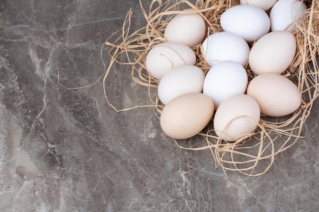 Несколько куриных свежих яиц на сене на мраморном фоне. фото высокого качества