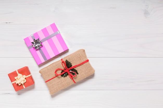 白い素朴な木の背景にいくつかのクリスマスプレゼント