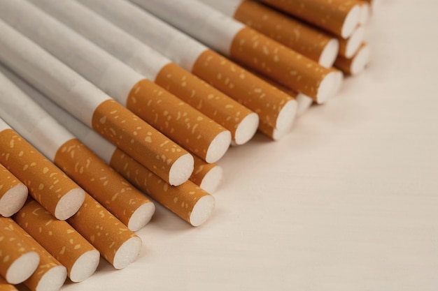 Several cigarettes are stacked on a white background and are dangerous for smokers.