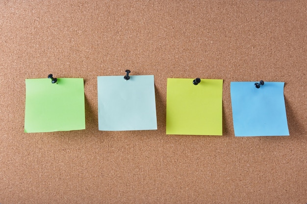 Several colored note sheets pinned to the cork board, copy space