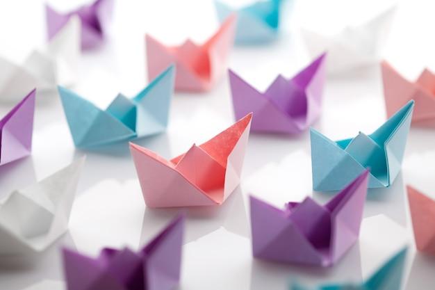 Несколько цветных бумажных корабликов на белом фоне.