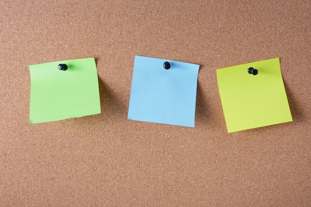 Several colored stickers for notes pinned to the cork board
