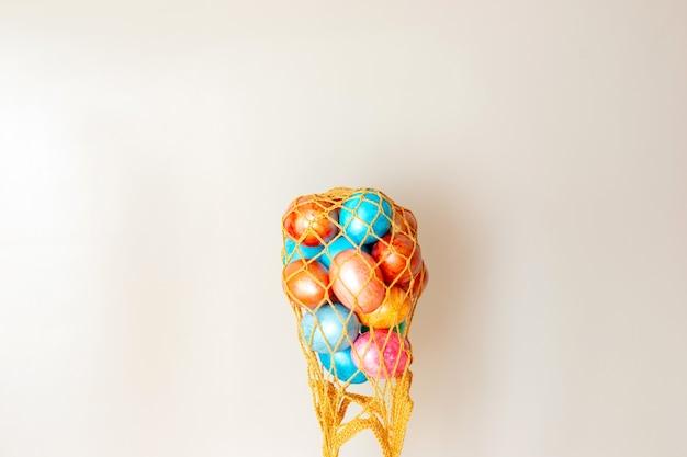 Несколько разноцветных яиц в перевернутой золотой вязаной сумке