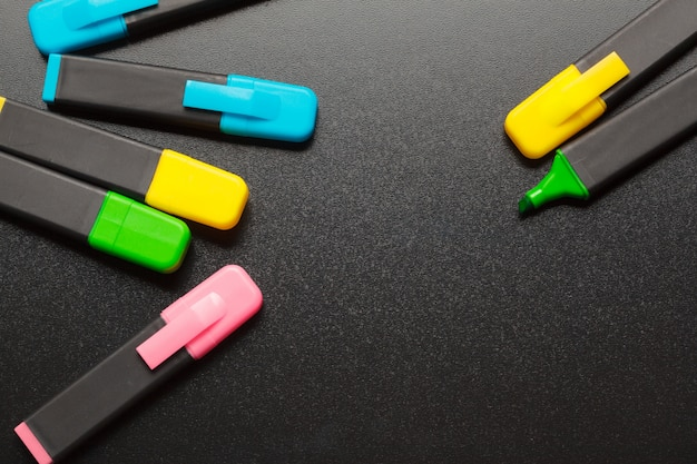 Several colorful highlighters on black desk close up
