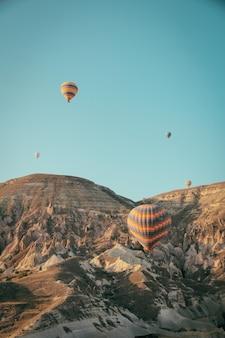 산 위에 떠있는 여러 다채로운 뜨거운 공기 풍선