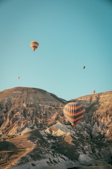 Several colorful hot air balloons floating above mountains