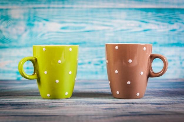 Several colorful tea cups on blue vintage background