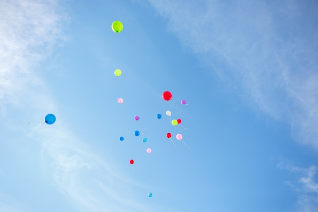Several coloured air balloons are flying into the blue sky