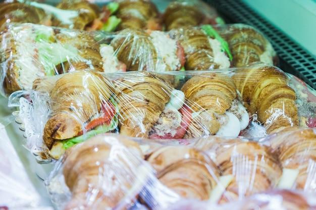 Несколько круассанов, фаршированных салатом из тунца и помидорами, выставлены на продажу