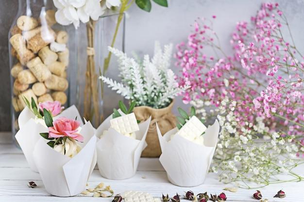흰색 나무 테이블에 흰색 버터 크림과 활기찬 핑크 장미와 함께 여러 컵 케이크와 머핀.
