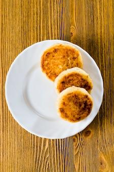 白い皿の上に横たわるいくつかの豆腐チーズケーキ、食べ物のクローズアップ、東スラブ料理